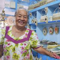 Gradle Alfred shows off handicrafts on display at her shop in Majuro in late November. | KYODO