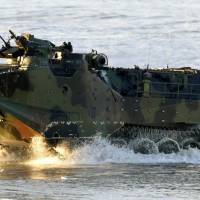 A U.S.-made AAV-7 amphibious vehicle rumbles onto the beach at the U.S. Marines' Camp Pendleton in California in February 2015. A delay in delivery to the Ground Self-Defense Force means Japan's new amphibious unit will launch in March with only seven AAV-7s. | KYODO
