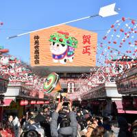 A giant ema (wooden votive plaque) with an illustration of next year's Chinese zodiac sign — the dog — is displayed above the shopping arcade at Sensoji Temple in Tokyo on Monday. | YOSHIAKI MIURA