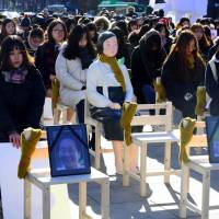 People sit around a statue of a 'comfort woman' in Seoul on Wednesday, during a performance event featuring empty chairs to represent eight former sex slaves who died this year. | AFP-JIJI