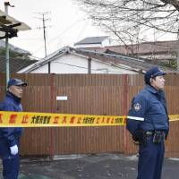 Police officers stand guard Monday in front of a house in Neyagawa, Osaka Prefecture, where a 33-year-old woman was reportedly confined for 15 years by her parents. | KYODO