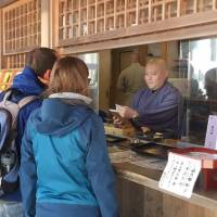 Foreign visitors pay entrance fees with credit cards at Kongobuji, the head temple of Koyasan Shingon Buddhism, on Mount Koya in Wakayama Prefecture. | KYODO