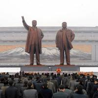 People place wreaths at the statutes of former North Korean leaders Kim Il-sung and Kim Jong-un in this photo released by North Korea's Korean Central News Agency in Pyongyang on Dec. 24. A plan to acquire long-range cruise missiles capable of striking North Korea could set off heated debate in the Diet next year. | KCNA / VIA REUTERS