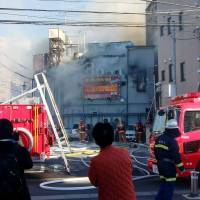 Firefighters try to extinguish a burning 'soapland' sex parlor in the city of Saitama on Sunday in this photo provided by a local resident. The establishment's phone number has been blurred out.  | KYODO