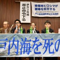 Residents who filed an injunction to suspend the restart of a reactor at the Ikata nuclear power plant speak at a news conference Wednesday in Hiroshima. | KYODO