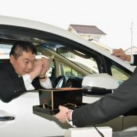 A funeral home employee on Saturday demonstrates how mourners in cars will be able to offer incense using a drive-thru window at the Aishoden funeral home in Nagano Prefecture. | KYODO