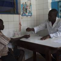 A doctor in Cote d'Ivoire distributes the anti-worm medication praziquantel to a child as part of a clinical trial. | COURTESY OF THE GHIT FUND