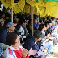People opposed to the relocation of the U.S. Marine Corps' Futenma Air Station in Ginowan, Okinawa Prefecture, to Nago, also in the prefecture, take part in a rally in front of Camp Schwab in Nago on Tuesday as the sit-in protest reached 5,000 days. | KYODO
