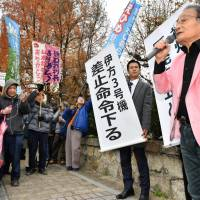 A lawyer representing residents who filed an injunction to suspend reactor operations at Ikata nuclear power plant speaks in front of Hiroshima High Court on Wednesday, after the court revoked a lower court decision and ordered suspension of the No. 3 reactor. | KYODO
