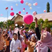 Students release balloons into the sky during a tree-planting event Friday at an elementary school in Banda Aceh, Indonesia, which was devastated by the 2004 Indian Ocean tsunami. | KYODO