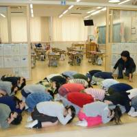 Elementary school students in Fukuoka take part in a missile drill in the city on Friday. | KYODO