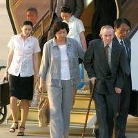 Former U.S. Army Sgt. Charles Jenkins and his wife, Hitomi Soga, a former Japanese abductee to North Korea, arrive at Tokyo's Haneda airport with their two North Korean-born daughters in July 2004. Jenkins died in Japan on Monday at age 77. | KYODO