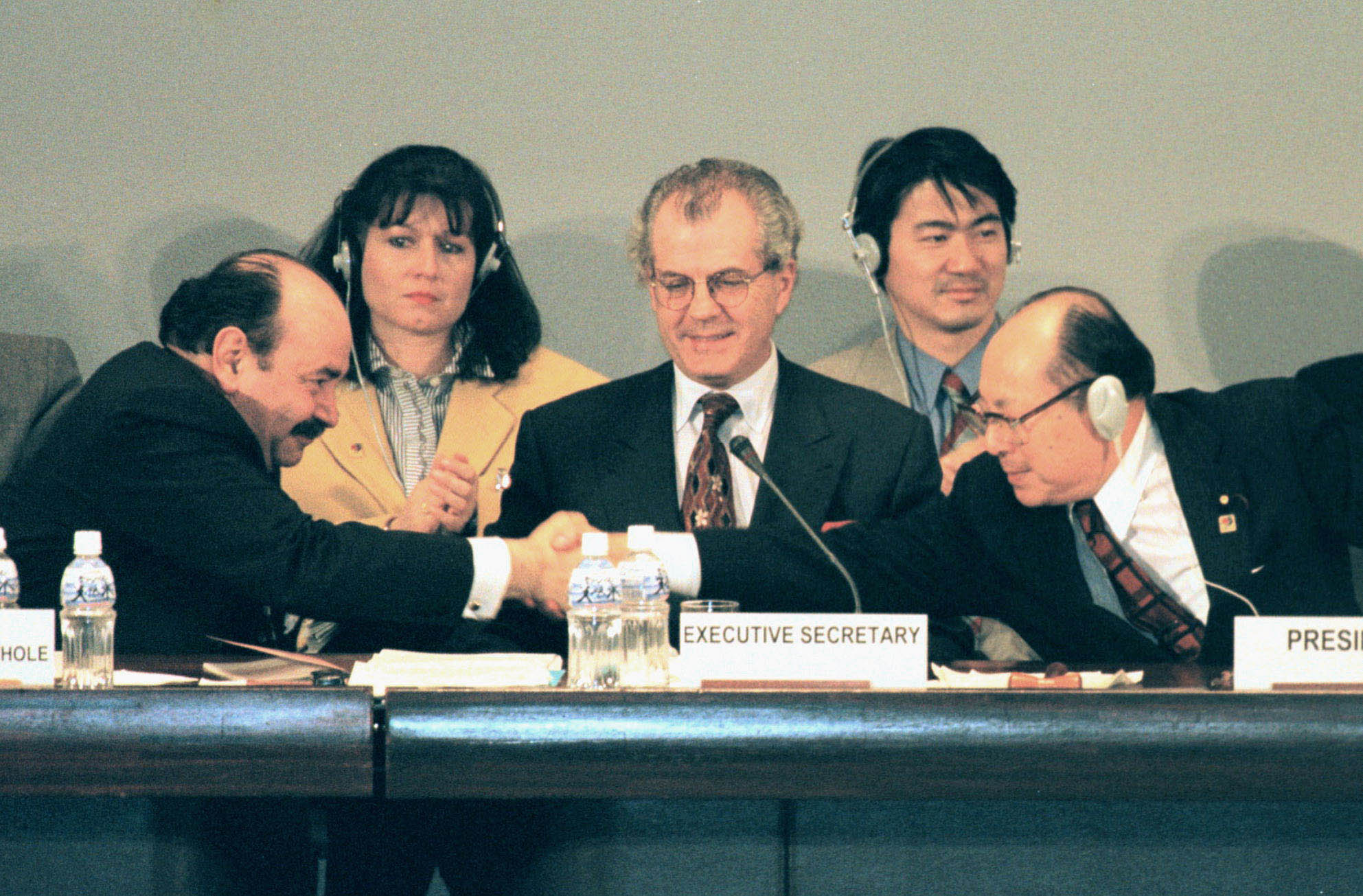 Raul Estrada, chairman of the third Conference of the Parties to the U.N. Framework Convention on Climate Change (COP3), shakes hands with Japan's environment chief, Hiroshi Oki, as the Kyoto Protocol is adopted in the ancient capital in December 1997.   KYODO