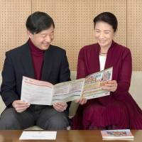 Crown Prince Naruhito and Crown Princess Masako look at a pamphlet about the Week of Persons with Disabilities on Dec. 5. | KYODO