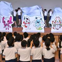 Three sets of mascot designs for the Tokyo 2020 Games, chosen from 2,042 submissions from professional and amateur designers, are unveiled as finalists during a ceremony at Kakezuka Elementary School in Tokyo on Thursday. Voting by elementary school pupils nationwide will be held over the next few months before the winner is announced on Feb. 28. | YOSHIAKI MIIURA