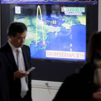 A large TV monitor set up in the Yurakucho district of Tokyo shows news of North Korea's missile launch on Nov. 29. | KYODO