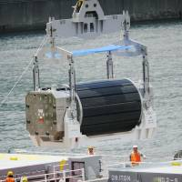 A canister of MOX uranium-plutonium mixed oxide fuel is unloaded from a transport vessel at Kansai Electric Power Co.'s Takahama nuclear plant in Fukui Prefecture in June 2010. | KYODO