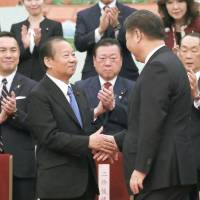 Japanese ruling party heavyweight Toshihiro Nikai (left) shakes hands with Chinese President Xi Jinping during their meeting Thursday in Beijing. | KYODO
