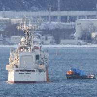 A North Korean fishing boat (center) taken into custody on Nov. 28 by the Japan Coast Guard off Matsumae, Hokkaido, attempts to escape from its escort (left) on Friday near Hakodate port. | KYODO