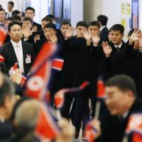Members of the North Korean men's national soccer team are greeted by compatriots upon arriving at Tokyo's Haneda airport on Tuesday for the E-1 Football Championship tournament. | KYODO
