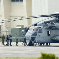 A CH-53E helicopter that accidentally dropped a window onto an elementary school playground Okinawa is parked at nearby Futenma air base in Ginowan on Thursday. | KYODO