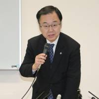 Yoshihiro Kizawa, an Osaka University trustee, faces reporters Tuesday to explain the cyberattacks that led to the university's massive personal data leak. | KYODO
