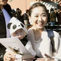 A women with her baby dressed up in a panda costume is all smiles after she sees Xiang Xiang, a panda cub making its public debut on Tuesday at Ueno Zoo in Tokyo. | KYODO