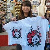 A clerk at a souvenir shop on the Ameyoko shopping street in Ueno holds limited-edition T-shirts of panda cub Xiang Xiang. | CHISATO TANAKA