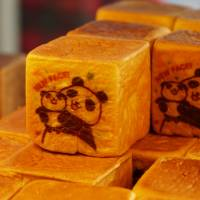 Cube-shaped loafs bearing the image of a mother panda holding her baby are displayed at a bakery across from JR Ueno Station. | CHISATO TANAKA