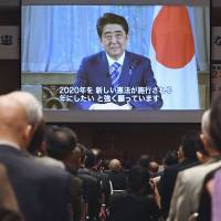 Participants at a gathering of people seeking to amend the Constitution watch a video message from Prime Minister Shinzo Abe in June in Tokyo's Chiyoda Ward. | KYODO