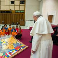 Pope Francis is presented with a gift from a group of children during a special meeting to celebrate his birthday at Paul VI hall at the Vatican Sunday. | OSSERVATORE ROMANO / HANDOUT / VIA REUTERS