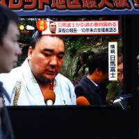 People walk past a street monitor showing Sumo grand champion Harumafuji in Tokyo on Wednesday. | REUTERS