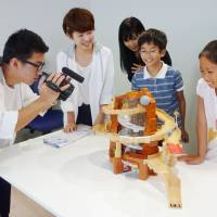 Parents and children participate in an event organized by Uuum Co. to experience video production with top-class YouTubers, at the Roppongi Hills complex in Tokyo in July 2016. | KYODO