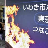 A signboard welcoming the torch relay for the 2020 Tokyo Olympics is seen in front of the Iwaki Municipal Government building in Fukushima Prefecture in August. | KYODO