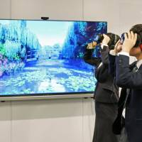 JTB System Solution employees view a painting by Claude Monet with virtual reality at a press briefing on Nov. 7 in Tokyo. | KYODO