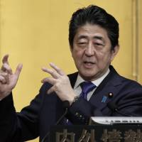 Prime Minister Shinzo Abe gestures as he speaks at an event Tuesday hosted by the Research Institute of Japan in Tokyo. | BLOOMBERG