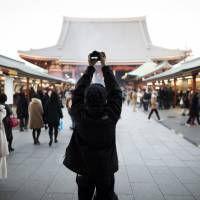 The perfect shot: A tourist takes a photograph at Sensoji Temple in Tokyo's Asakusa district in January. | BLOOMBERG