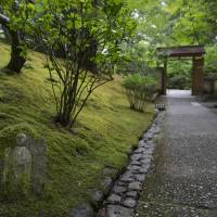 A moss-covered statue lies next to a path in the Portland Japanese Garden. | CHRISTINA SJOGREN