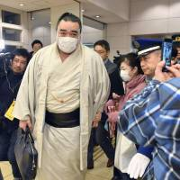 Sumo-size trouble: Harumafuji makes his way through a gaggle of reporters and photographers after a news conference in November where he announced his retirement from sumo wrestling. | KYODO