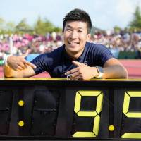 Fast feet: Yoshihide Kiryu points to his record-breaking time after finishing the 100-meter race at a meet in Fukui Prefecture in September. | KYODO