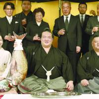 Kisenosato holds up a red sea bream during a formal ceremony in which he was officially promoted to the rank of yokozuna. | KYODO