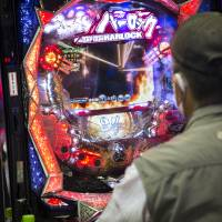 Ball and chain: A customer plays a pachinko machine in Tokyo in May. | BLOOMBERG