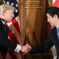 Different strokes: U.S. President Donald Trump and Prime Minister Shinzo Abe shake hands after a press conference in Tokyo on Nov. 6. During his visit Trump said Japan should be buying more military hardware from the U.S., but the nation has its own plans. | POOL / KYODO