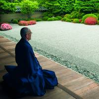 Garden meditations: A monk looks out at a rock garden at a temple in Kyoto. | PHOTOGRAPH BY JOHN EINARSEN, © PERIPLUS EDITIONS (HK) LTD.