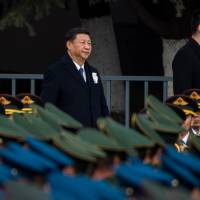 Chinese President Xi Jinping, shown  attending a Dec. 13 memorial ceremony at the Nanjing Massacre Memorial Hall, has indicated a desire for better Japan-China relations. But the two countries will likely remain regional rivals. | AFP-JIJI