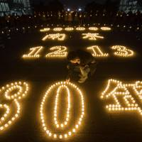 Students light candles at Nanjing Normal University on Dec. 11 during a ceremony ahead of China's Dec. 13 National Memorial Day for Nanjing massacre victims in Nanjing. | AFP-JIJI