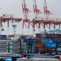 Containers sit stacked next to gantry cranes at a Yokohama shipping terminal in March. Japan is the world's fourth-largest export economy, but only 25 percent of its small and medium-size manufacturers sell their products abroad. | BLOOMBERG