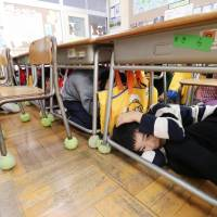 A new routine: First graders at an elementary school in Morioka, Iwate Prefecture, shelter under their desks during an emergency drill in November simulating a ballistic missile-launch scenario from North Korea. | KYODO