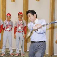 Batting a thousand: Japanese Prime Minister Shinzo Abe takes a swing in a meeting with members of the Tokyo Kitasuna baseball team at his office in Tokyo on Dec. 11. The baseball team visited Abe after winning the Little League World Series title in August. The prime minister saw a big win this year in the October general election. His ruling coalition won more than two-thirds of the seats in the Lower House. | KYODO