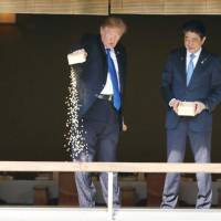 All you can eat: U.S. President Donald Trump (left) and Prime Minister Shinzo Abe feed carp in a pond at the Akasaka Palace state guesthouse in Tokyo in November. This image went viral as many online pointed out you shouldn't feed carp so much food in one go, but it was later learned that the U.S. president was just following the lead of his host. | KYODO